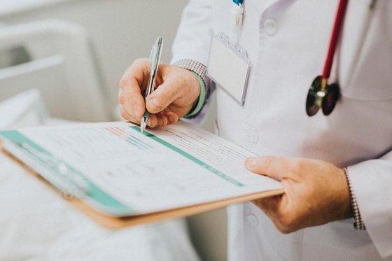 Лекар, записващ оплаквания.